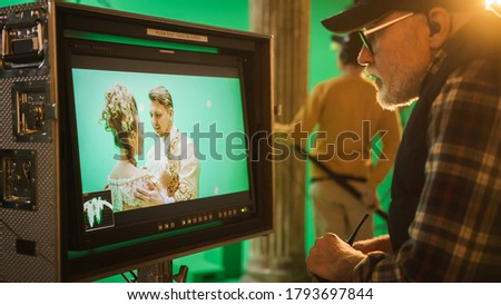 Director Looks at Display Controls Shooting Period Drama Movie. Green Screen CGI Scene with Actors Wearing Renaissance Costumes. Crew Shooting High Budget Movie. Stockfoto ©