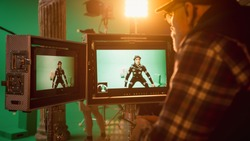 Director Looks at Displays Directs Green Screen CGI Scene with Actor Wearing Motion Tracking Suit and Head Rig. In the Big Film Studio Professional Crew Shooting Blockbuster Movie