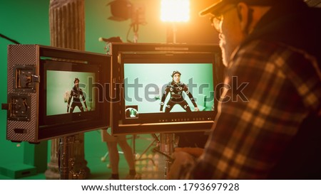 Director Looks at Displays Directs Green Screen CGI Scene with Actor Wearing Motion Tracking Suit and Head Rig. In the Big Film Studio Professional Crew Shooting Blockbuster Movie Сток-фото ©
