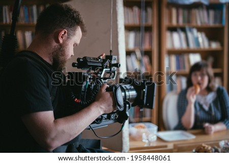 Director of photography with a camera in his hands on the set. Professional videographer at work on filming a movie, commercial or TV series. Filming process indoors, studio