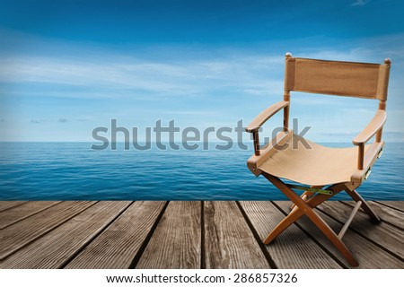 Director\'s chair on the wood and blue sea background