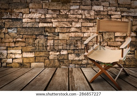 Director\'s chair on the wood and brick background