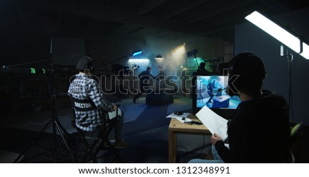 Director watching actors playing fight scene while shooting movie on stage set