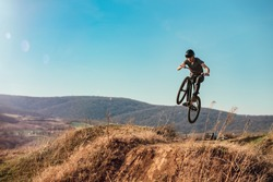Dirt bike rider jumping in bike park on mountain bike