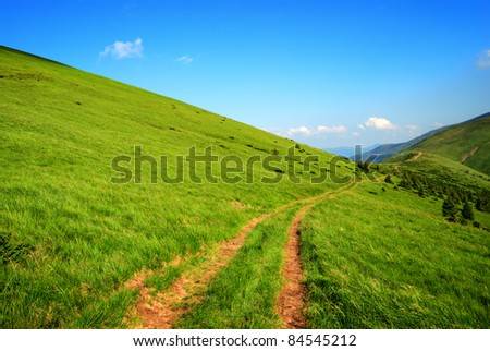 dirt long road among green hills and blue sky