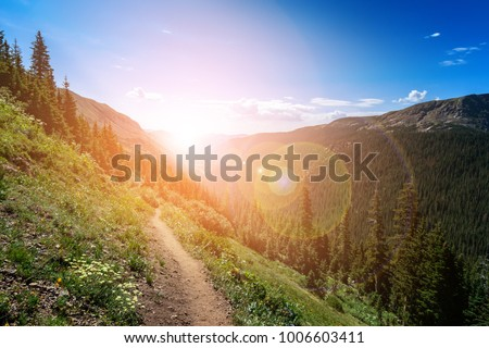 Dirt path hiking trail climbs through the Colorado mountains with the colorful light of the bright sun shining over the distant horizon