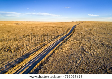 dirt ranch road  in Pawnee National Grassland in northern Colorado, fall or winter scenery, aerial view
