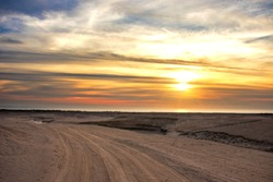 dirt road and a sunset on the sea