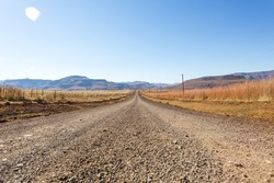 dirt road leading nowhere, mountain background, lens flare