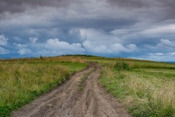 Dirt road leading to the top of the hill, dramatic storm clouds at summertime in Transylvania, Romania.