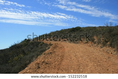 Dirt road leading up a hill side beneath blue sky with clouds, Malibu, CA