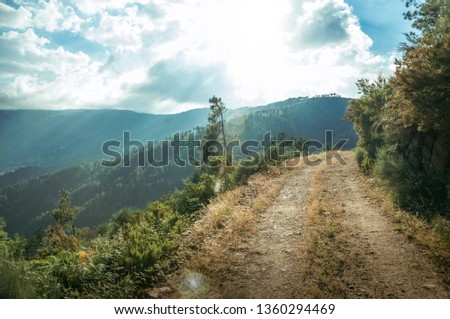 Dirt road on hilly terrain covered by bushes and green valley, in sundown at the highlands of Serra da Estrela. The highest mountain range in continental Portugal. Retouched photo. #1360294469