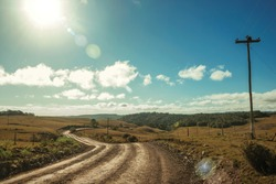 Dirt road passing through rural lowlands called Pampas with hills and sunlight near Cambara do Sul. A small country town in southern Brazil with amazing natural tourist attractions. Retouched photo.