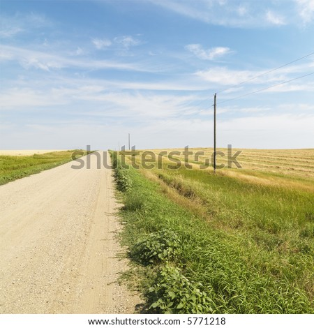 Dirt road through rural farmland of the American midwest. - stock photo