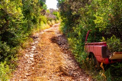 Dirt road through the bushes with old abandoned inside the bush red tender car body carcass on the mountains of Campania region in Italy