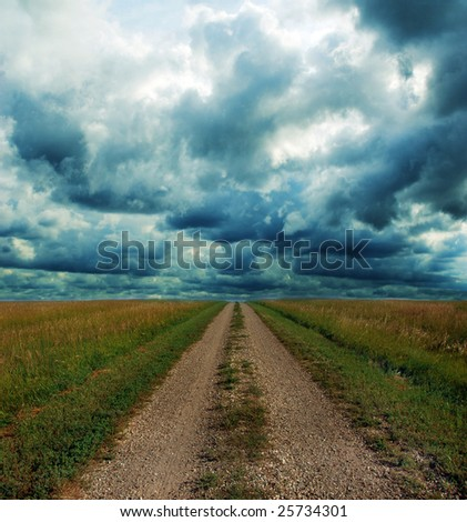 Dirt road through the prairie lands of the American Mid-West with Stormy Clouds.
