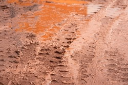 Dirt terrain road with wheel track on wet muddy surface. Transportation and road way, background and texture photo. Selective focus at the center part.