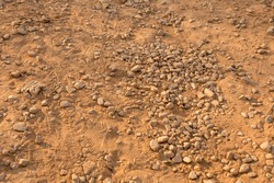 Dirt texture with small rocks and dust in brown colour