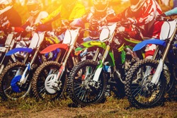 Dirtbike racers on motorcycles are at start, close-up, wheels are in row