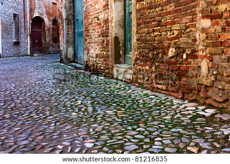 dirty alley in the old town with pavement of porphyry cobblestones