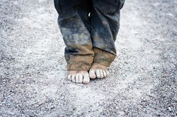 dirty and bare child's feet on gravel. Poverty concept