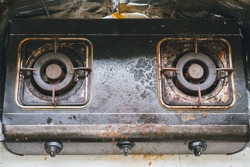 Dirty and grimy gas stove with cooking oil stains and burned food remnants on a surface of a gas stove in the kitchen.