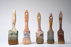 Dirty and old paintbrushes on gray background.