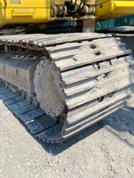 Dirty and rusty excavator track pad and grouser pad with top carrier rollers and track chain with sprocket at construction site