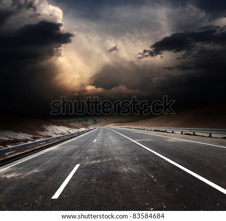 Dirty asphalt road and dark thunder clouds