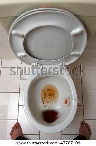 dirty bathroom with a toilet bowl full of vomit