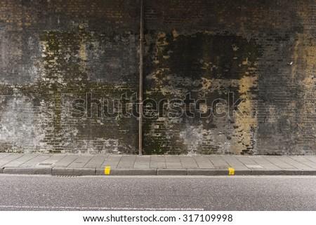 Dirty brick wall under the bridge.