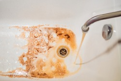 Dirty brown running water falling into a white sink from tap. Environmental pollution concept.