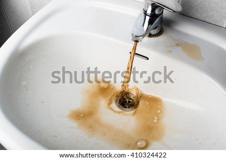 Dirty brown water running into a white sink. Looks very unhealthy,