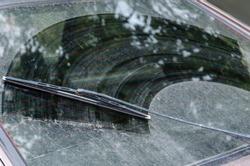 Dirty car window with a wiper blade