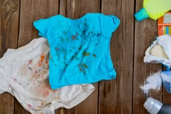 Dirty children's clothes are scattered on a wooden table next to washing powders and soap.Concept washing dirty spots, the best means of cleaning kids clothes.