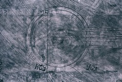 Dirty concrete floor with numbers in industrial warehouse building. Circle tire tracks of truck.