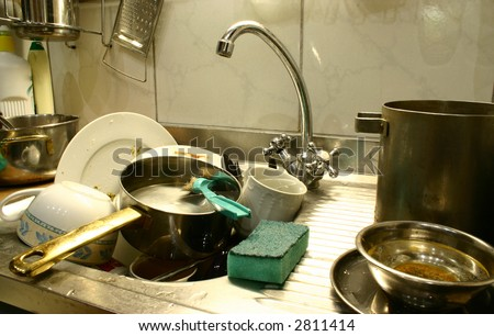 Dirty dishes in the kitchen\'s sink ready to start washing