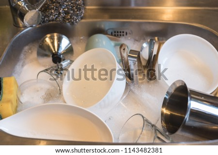 dirty dishes in the kitchen sink with water at home #1143482381