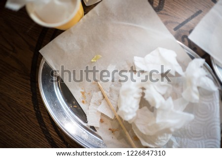 dirty dishes on a table in a restaurant. a lot of paper #1226847310