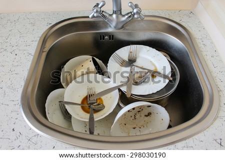 Dirty dishes: plates, cup, forks, spoons in the sink