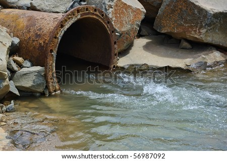 Dirty drain polluting a river. This pollutan comes from factory