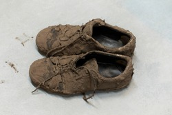 Dirty dried muddy and messy sneaker shoes totally covered with mud looking unrecognizable while laying on the floor
