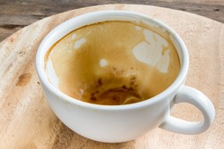 dirty empty coffee cup after drink on wooden plate