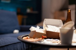 Dirty empty living room with food trash, bottle of beer and napkins on blue sofa. Unorganized house apartment of lonley woman with anxiety depresion having garbage, rubbish with no people in