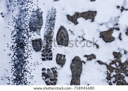 Dirty footprints in the snow in the winter.  #758945680
