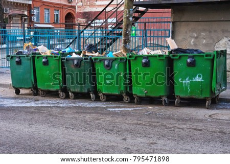 Dirty garbage jugs on a big city street full of waste