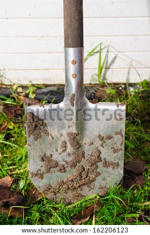 dirty garden spade stuck in the ground on a white wooden background