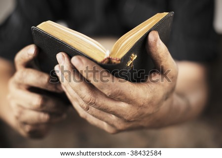 Dirty hands holding an old bible. Very short depth-of-field