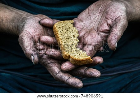 Dirty hands homeless poor man with piece of bread in modern capitalism society