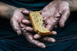 Dirty hands homeless poor man with piece of bread in modern capitalism society. Economic recession, unemployment, poverty, hunger, retirement, global crisis, 	inequality problem concept.